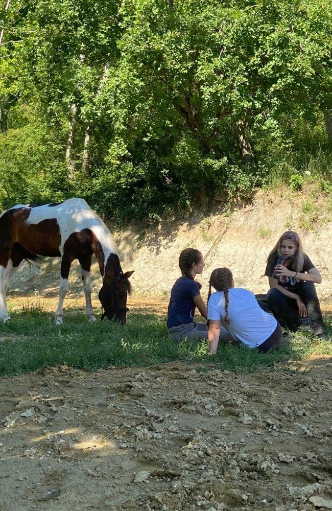 Konji na paši i deca odmaraju